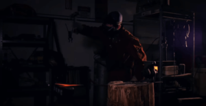 Someone hitting red hot metal with a hammer in a forge.